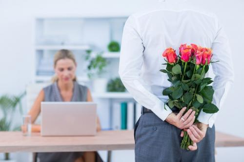 Businessman hiding flowers behind back to depict office romance
