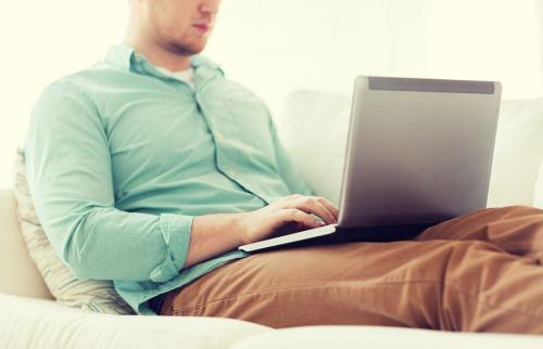 male employee sitting on couch with laptop, working from home