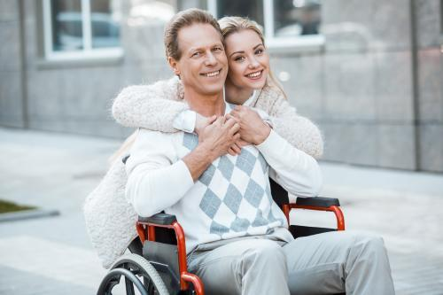 pic of pretty smiling woman hugging handsome smiling man in wheelchair, illustrates that discrimination against the woman might be a case of associative discrimination