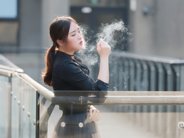 woman taking a smoke break from work, smoking a cigarette on outdoor walkway.