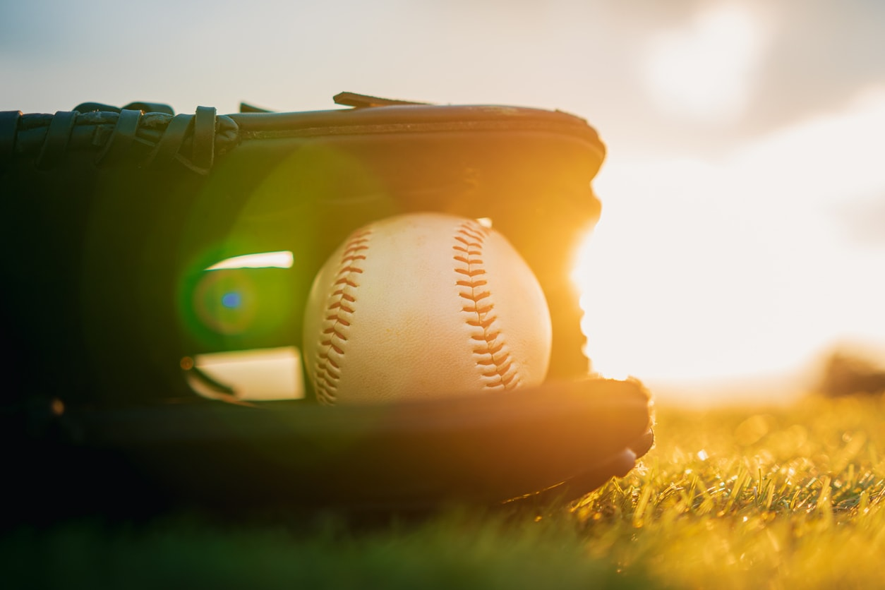 Three strikes policies mean everybody is out. baseball glove with ball lying in a field