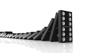 Black domino tiles falling in a row on to last one standing, iso