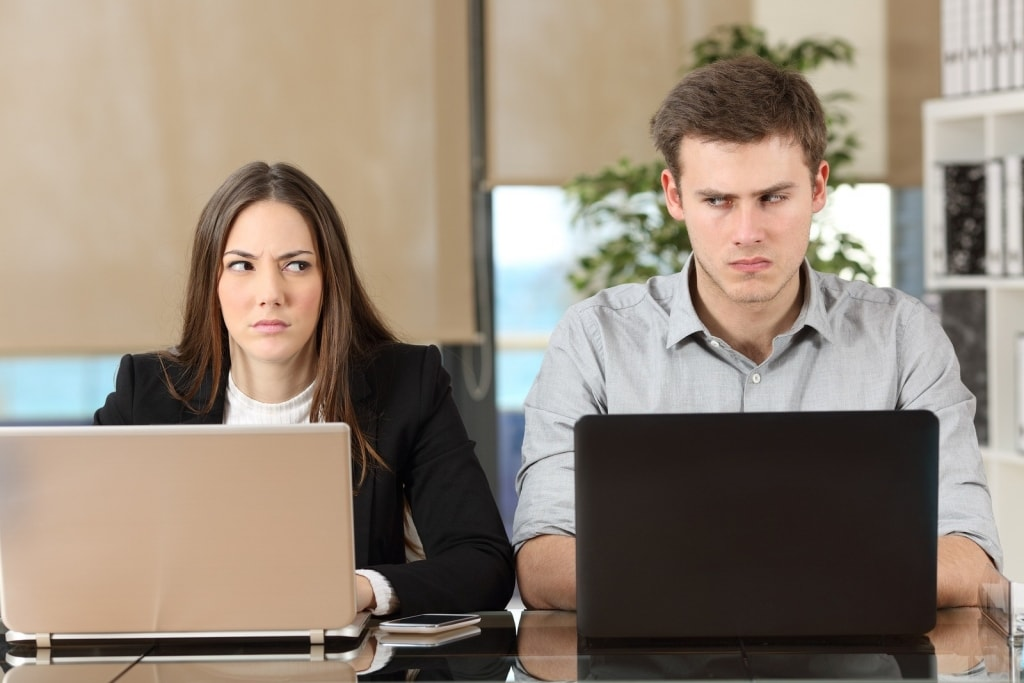 Front view of two employees using computers at workplace and looking sideways each other with anger to illustrate employee dispute