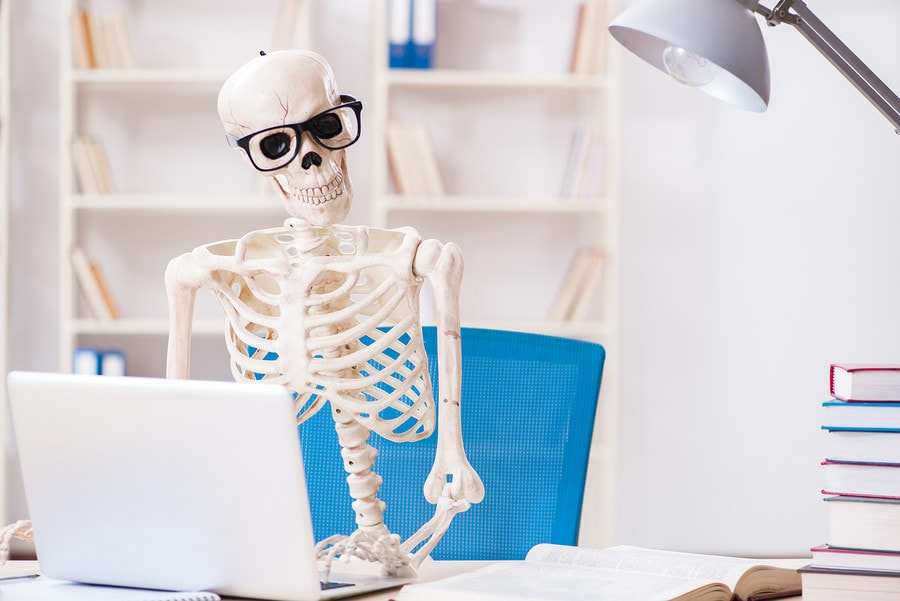 Skeleton businessman working in the office to illustrate HR-appropriate Halloween