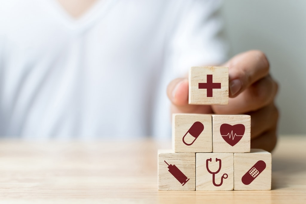 hand arranging wooden blocks with healthcare symbols to show employer health benefit options