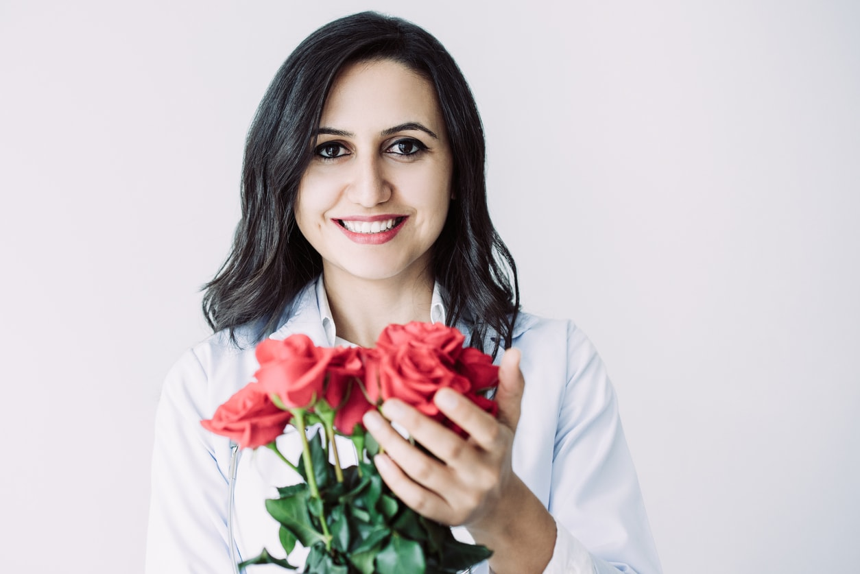Closeup portrait of smiling middle-aged beautiful dark-haired female doctor looking at camera and holding bunch of roses. Flowers for female doctor concept. Isolated front view on white background.