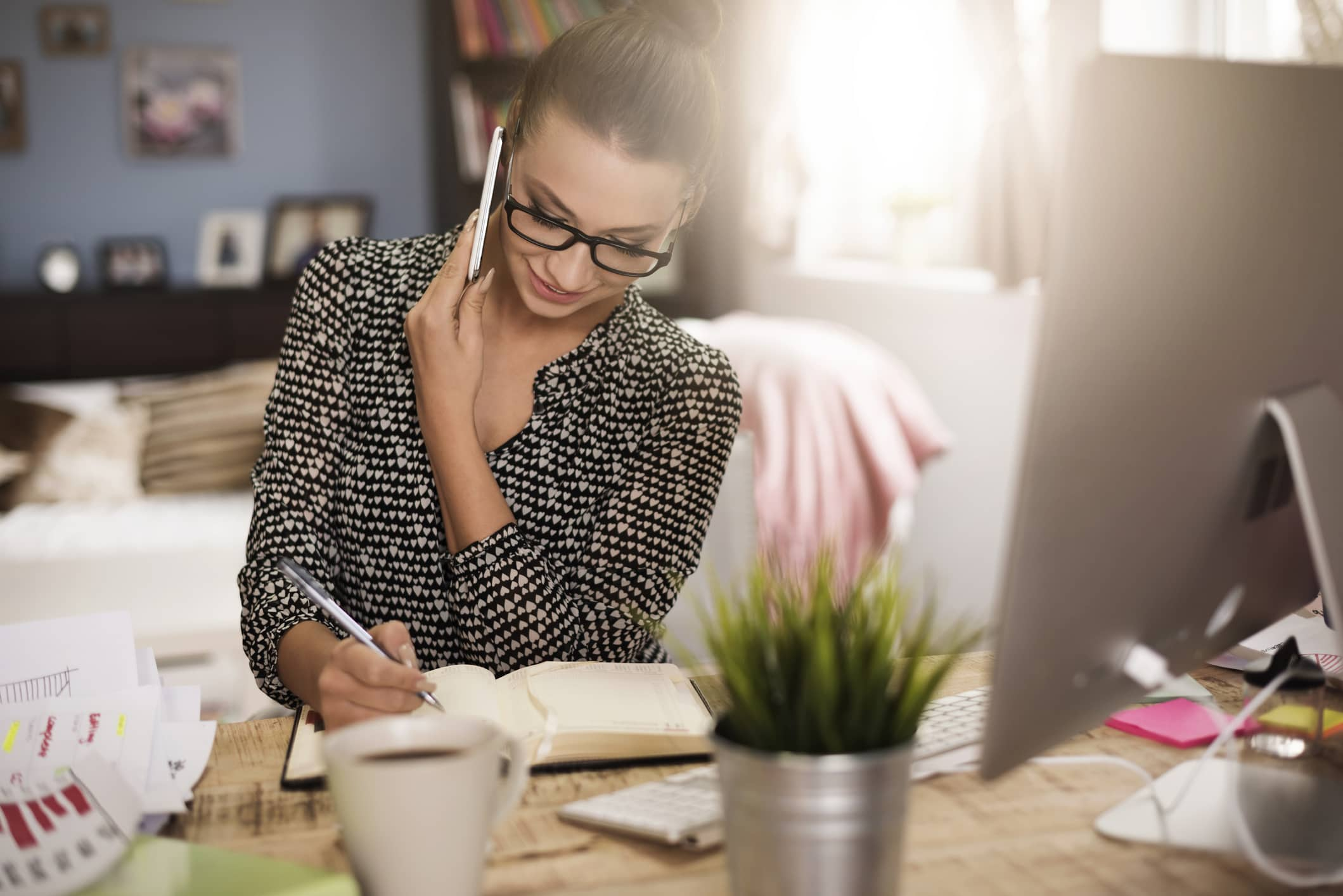 Blonde woman in glasses on the phone working in home office