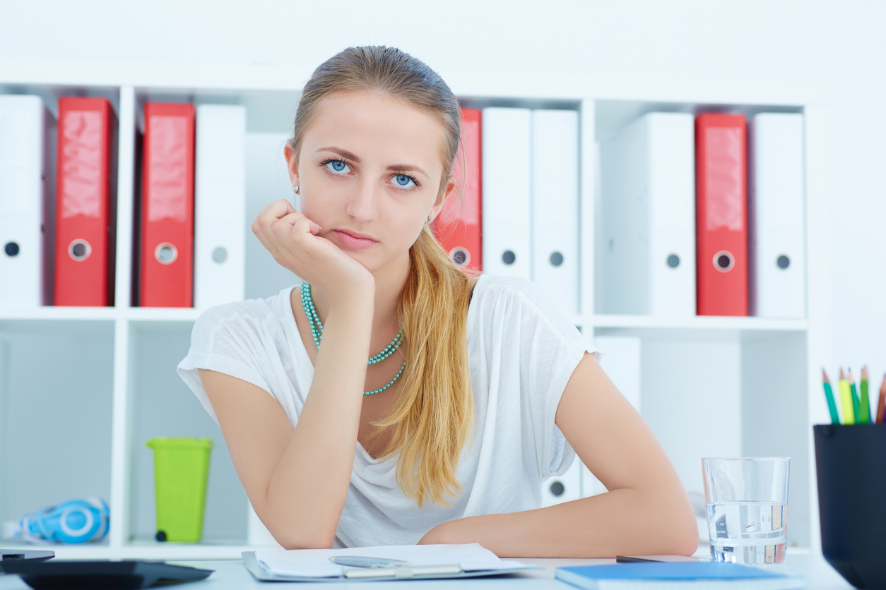 Beautiful tired girl sitting at the desk in the office and looking at the camera; employee would rather collect unemployment than work