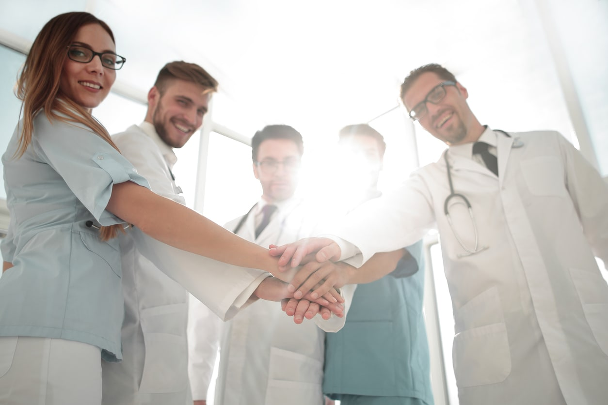 Medical dream team puts hands together while standing in a circle