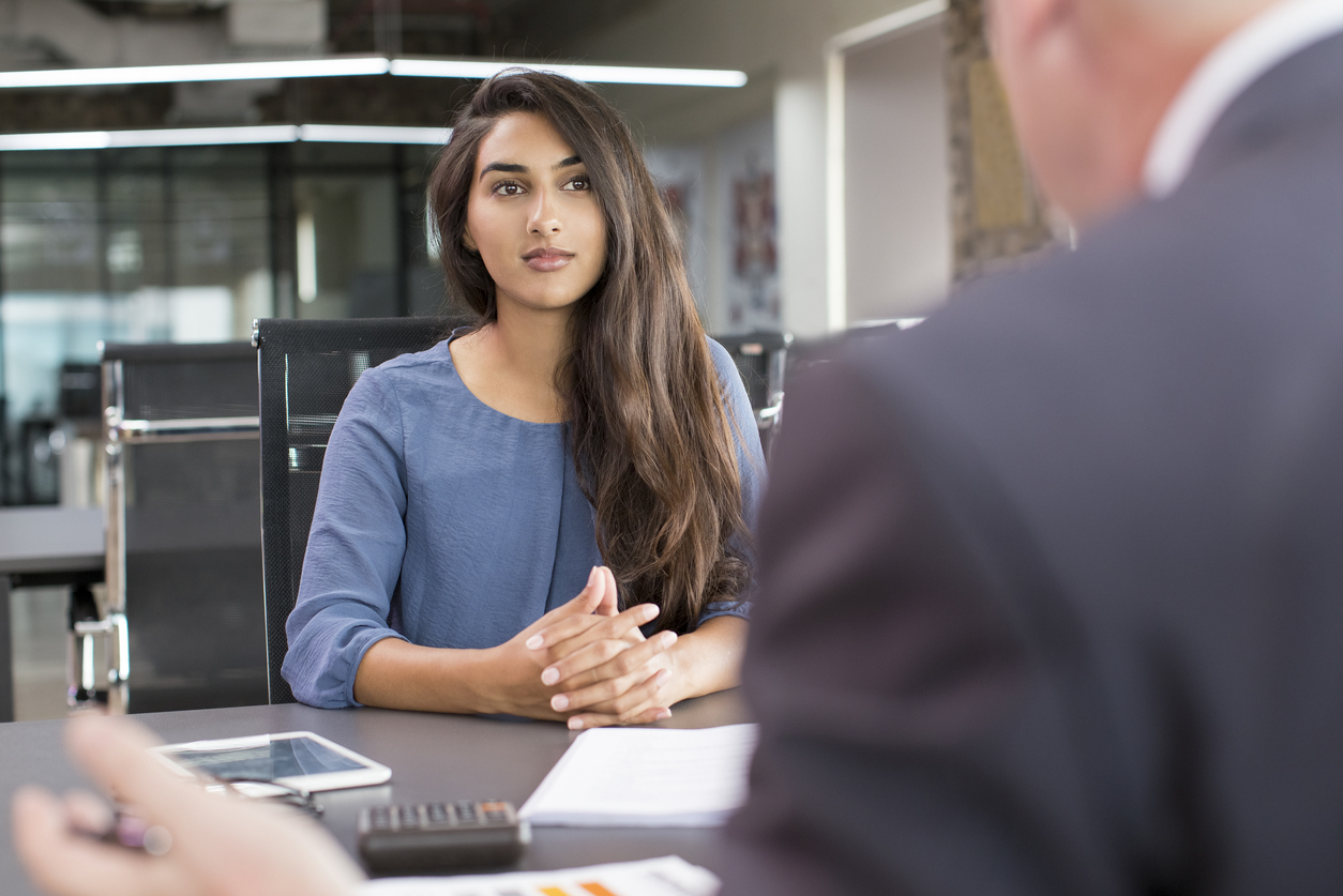 young woman in blue dress sits for a behavioral interview