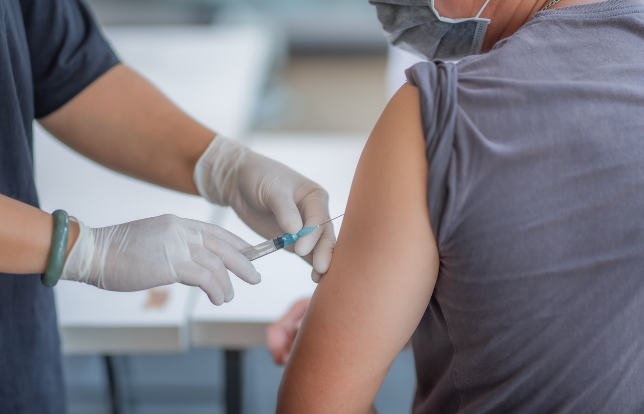 doctor injects healthcare worker with vaccine