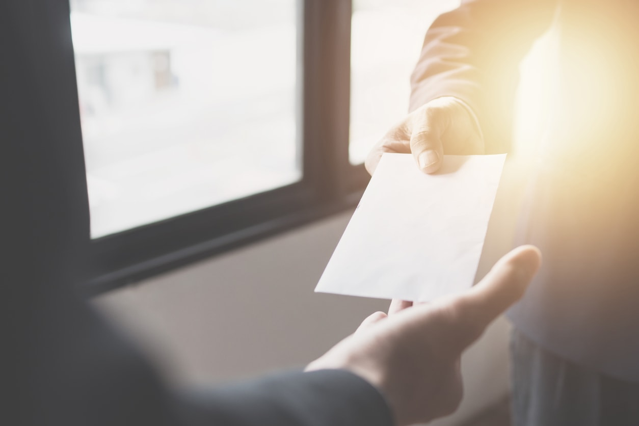 Close up hand of manager giving money bonus in paper envelope to happy employee