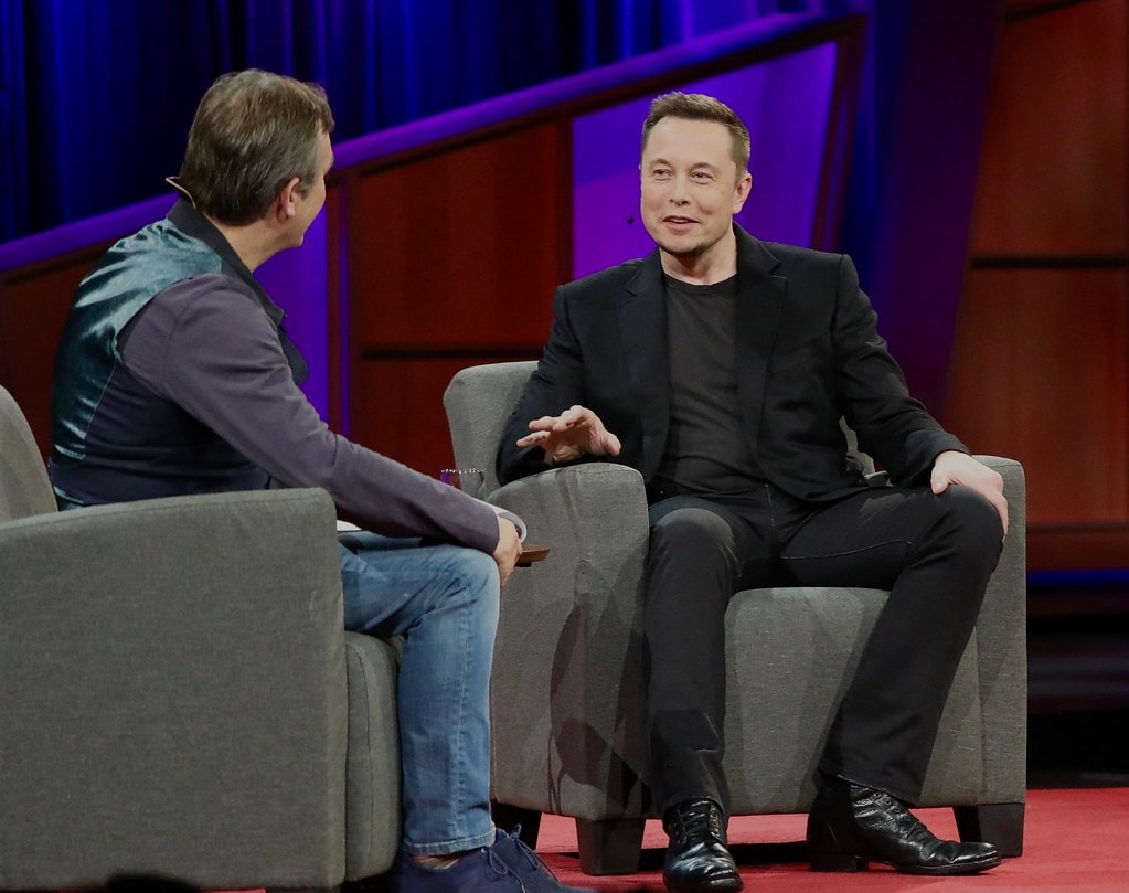 elon musk sits on stage during an interview